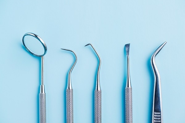 Dental Tool And Artificial Jaw Model For Dental Treatment On A Blue Background.